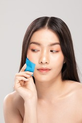 Beautiful Attractive Asian woman using Facial oil clean film to removal oily on face for face fresh skin feeling so fresh and clean,Beauty Concept,Isolated on grey background