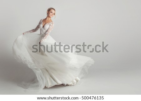 Beautiful attractive bride in wedding dress with long full skirt, white background, dance and smile