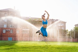 Beautiful, attractive, charming brunette having fun at the football stadium on a warm summer evening. Wrinkles from water from the field irrigation system, cooling under drops of water.