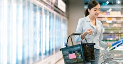 beautiful attractive cheerful asian housewife shopping in supermarket with smile and happiness hand pick fresh product or consumer stuff with abstract blue demartment mall background