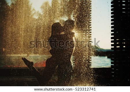 Beautiful attractive couple hugging and kissing under the jets of water in luxury spa hotel on honeymoon vacation in the tropics #523312741