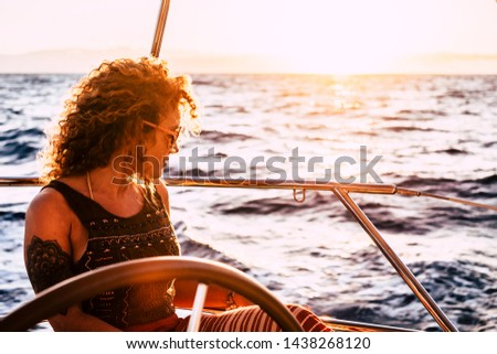 Beautiful attractive curly blonde adult woman looking the ocean enjoying a trip and travel on sail boat - modern generation people enjoy freedom and alternative lifestyle traveling #1438268120