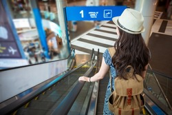 beautiful attractive female student arrived travel destination and taking the airport escalator going to transport station with back view photo.