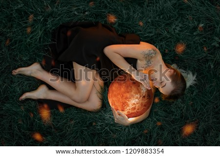 Beautiful attractive girl in a black dress embraces the planet Venus, a riddle on the grass, artistic photography, top view