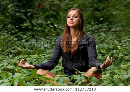 Beautiful attractive girl meditating outdoors in lotus pose