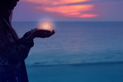 Beautiful attractive girl on a night beach with sand and stars holds the moon in her hands, Artistic Photography