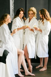 Beautiful attractive girls talking and drinking champagne in white coats on black wall background