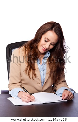 Beautiful attractive happy smiling corporate lawyer business woman sitting at desk and writing blank paper page, isolated.