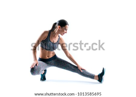 Beautiful attractive sportive athletic cute happy smiling cheerful sportswoman stretching her legs before running, isolated on white background