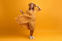 beautiful attractive stylish woman in yellow cotton dress posing on yellow bright background isolated, wearing straw hat summer fashion style trend