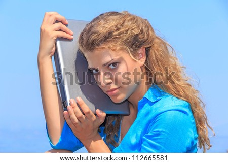 Beautiful attractive woman at the beach holding a laptop next to her face