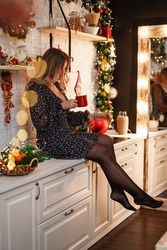 Beautiful attractive woman sitting in the kitchen decorated with Christmas lights with a mug and enjoying a hot drink in the evening kitchen decorated with Christmas lights. Preparing for the holiday.