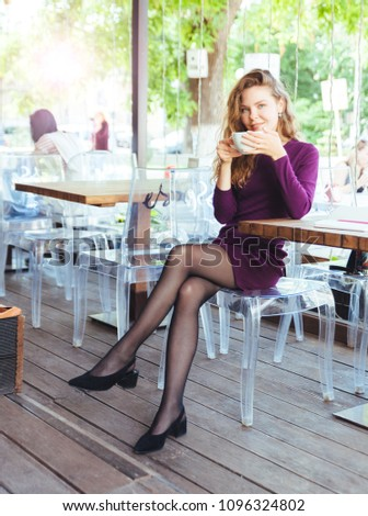 Beautiful attractive young blonde woman with curly hair drinking cappuccino and eating croissant in city cafe summer day. Notebook and telephone are on the table #1096324802