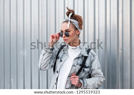 Beautiful attractive young hipster woman in a stylish bandana with a stylish hairstyle in fashionable sunglasses in a summer denim jacket with a backpack near the metal wall. Modern American girl.