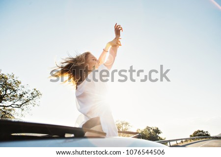 Beautiful, attractive young woman with blonde hair and in white tshirt stands up from cabriolet convertible car with sky light, puts arms in sky, catches wind of freedom and youth, excited and happy
