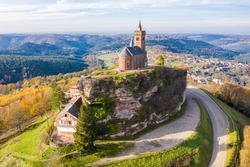 Beautiful autumn aerial view of St. Leon chapel dedicated to Pope Leo IX atop of Rocher de Dabo (Rock of Dabo), red sandstone rock butte, and Moselle-Vosges mountains and valleys. Lorraine, France.