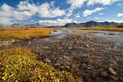 Beautiful autumn Arctic landscape. A small river in the tundra. Mountains in the distance. Travel and hiking in the wilderness in the Far North in the Polar Region. Nature of Chukotka. Far East Russia