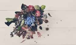 Beautiful autumn bouquet composition of dried roses and meadow flowers with leaves, floral background. Floristic art decoration closeup, top view with copy space