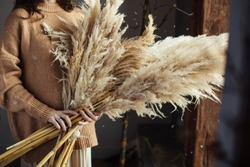 Beautiful autumn bouquet of dry materials in the hands of a woman. Cortaderia
