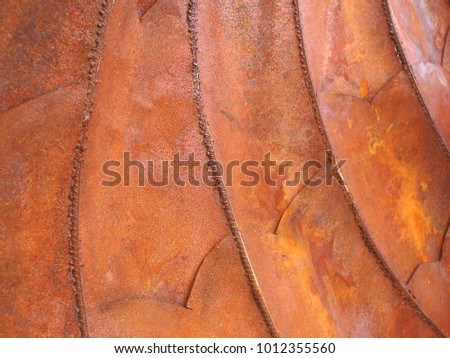 Beautiful autumn colored abstract metal texture close up of rusty welded ridges and colorful curves, orange, gold and brown dimensional with subtle chevron shapes #1012355560