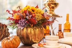 beautiful autumn composition in a pumpkin vase on a table
