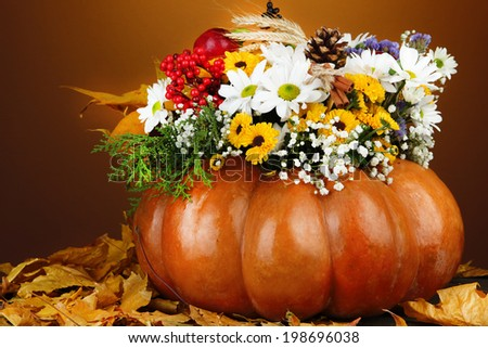 Beautiful autumn composition in pumpkin with yellow leaves on table on dark background #198696038