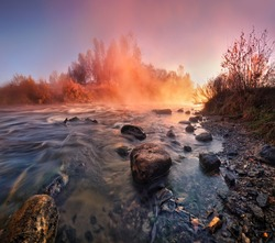 Beautiful autumn foggy morning on the fast river of Belarus in the light of rising sun.Summer misty sunrise on the river. Foggy river in the morning. Summer misty dawn. Foggy morning.