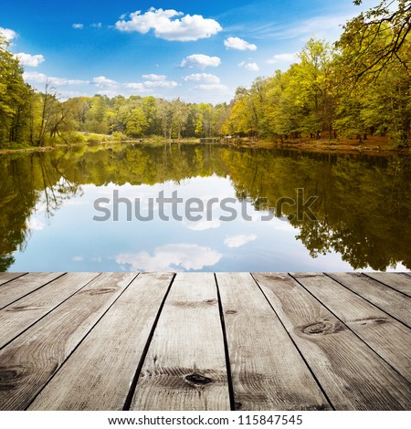 Beautiful autumn forest with reflection in the water and wood planks. Beauty nature background