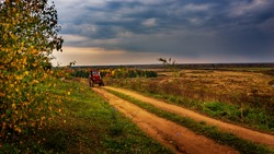 beautiful autumn landscape view from the hill a red tractor is moving along a rural road the end of agricultural work gave fields forests stormy sky