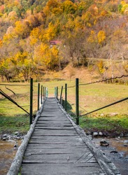 Beautiful autumn landscape with a wooden bridge over a mountain stream. Old wooden suspension bridge over a small mountain river. Wooden footbridge over a stream