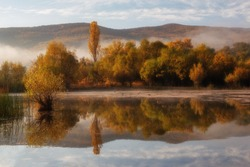 Beautiful autumn landscape with reflection in the lake. Fog on the lake on an autumn morning.