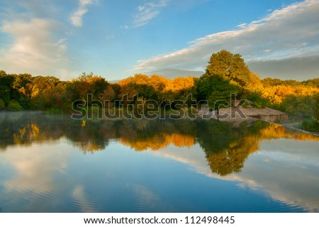 Beautiful autumn landscape with yellow trees reflection in water