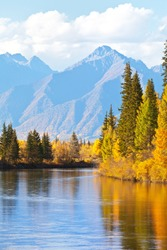 Beautiful autumn landscape with yellowed trees at the riverside and a mountain range on sunny afternoon. Siberia, Baikal region, Eastern Sayan Mountains,  Buryatia, Tunka foothill valley, Irkut Rive