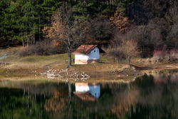 Beautiful autumn mountain landscape and reflection in the water of the chapel