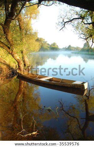 Beautiful autumn river and yellow rowing boat on a tranquil early morning