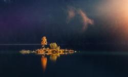 Beautiful autumn scene. Colorful foggy morning view of small island with trees under sunlit on lake, Magic atmothpheric landscape,  Amazing Nature background. Impressive Wild area. Creative Image.