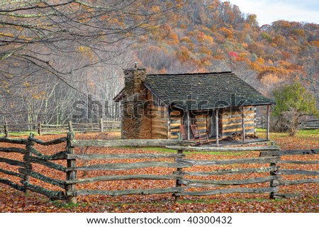 Beautiful Autumn scene showing rustic old log cabin surrounded by split rail fence - stock photo