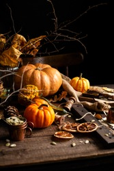 beautiful autumn still life with assorted pumpkins, bouquet of fall leaves and branches, pumpkin seeds, copper cups, dried orange slices, forks on rustic wooden brown table, autumn card, thanksgiving
