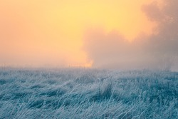 Beautiful autumn sunrise over cold foggy meadow. Textured grass foreground with hoar frost. October dawn.
