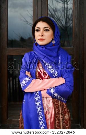 Beautiful azeri woman in traditional Azerbaijani dress standing at the wooden window outdoors. Novruz holiday celebration