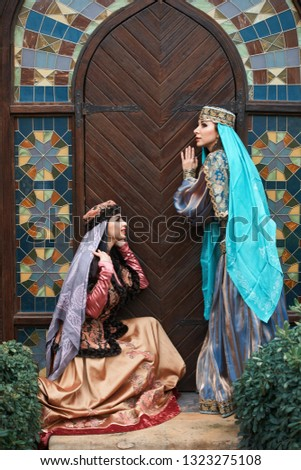 Beautiful azeri women in traditional Azerbaijani dress knocking the wooden door of an old house. Spring, Novruz holiday celebration concept