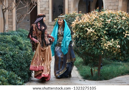 Beautiful azeri women in traditional Azerbaijani dress running by the wooden door of an old house. Spring, Novruz holiday celebration concept