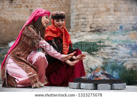 Beautiful azeri women in traditional Azerbaijani dress warming hands above the bonfire. Spring, Novruz holiday celebration concept