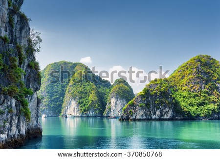 Beautiful azure water of lagoon in the Halong Bay (Descending Dragon Bay) at the Gulf of Tonkin of the South China Sea, Vietnam. Scenic landscape formed by karst towers-isles on blue sky background. #370850768