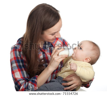 beautiful baby boy is feeding from bottle by his mother