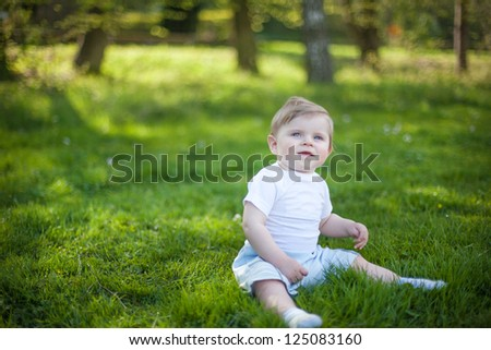Beautiful baby boy on green grass in summer forest