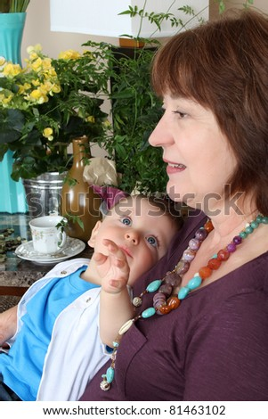 Beautiful baby boy sitting by his grandmother