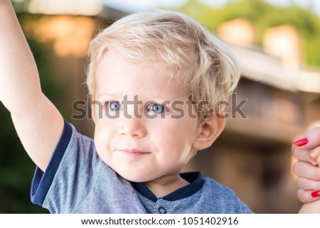 05deba22765 Beautiful baby boy with blue eyes and blond hair holding hands, natural  light close up