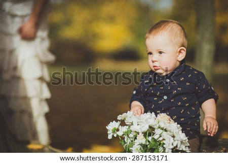 Beautiful baby crawling or sitting in fallen leaves. playing with flowers - fall scene