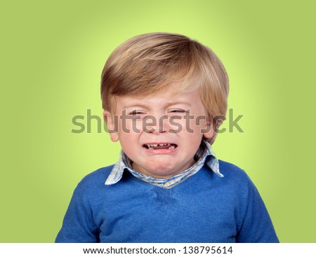 Beautiful baby crying isolated on green background